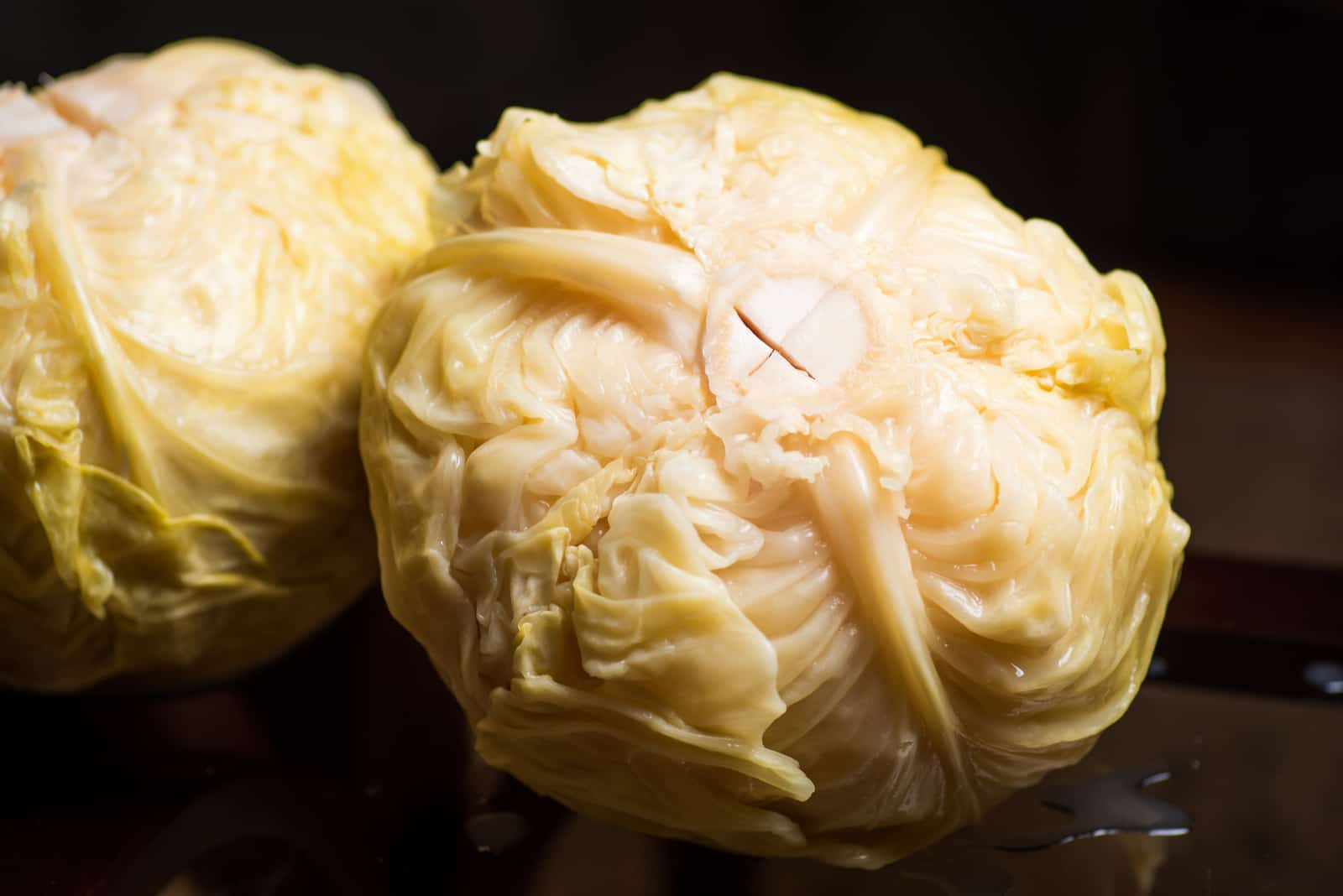 two pieces of sauerkraut stand on a black background