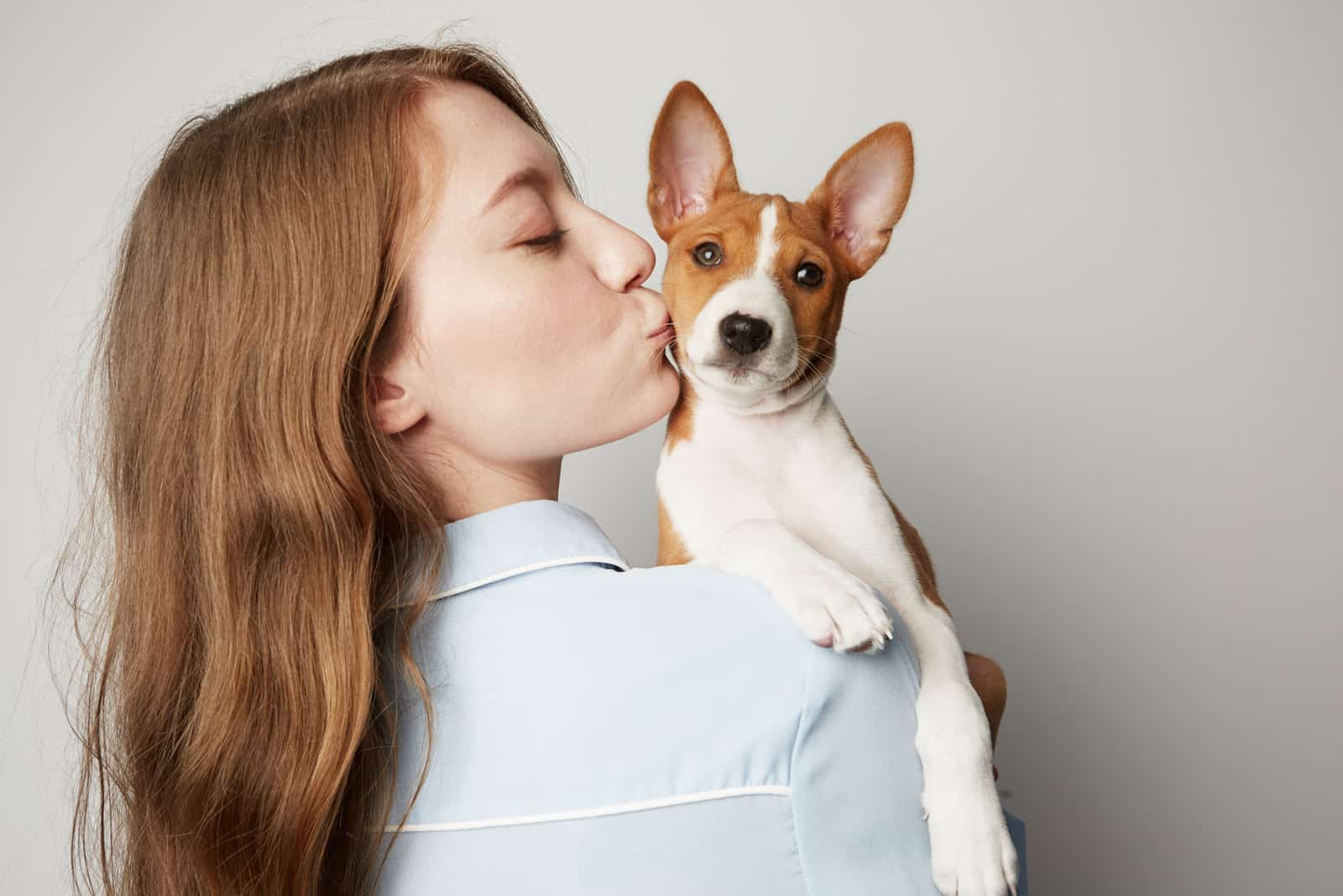 young woman hugging and kissing her puppy