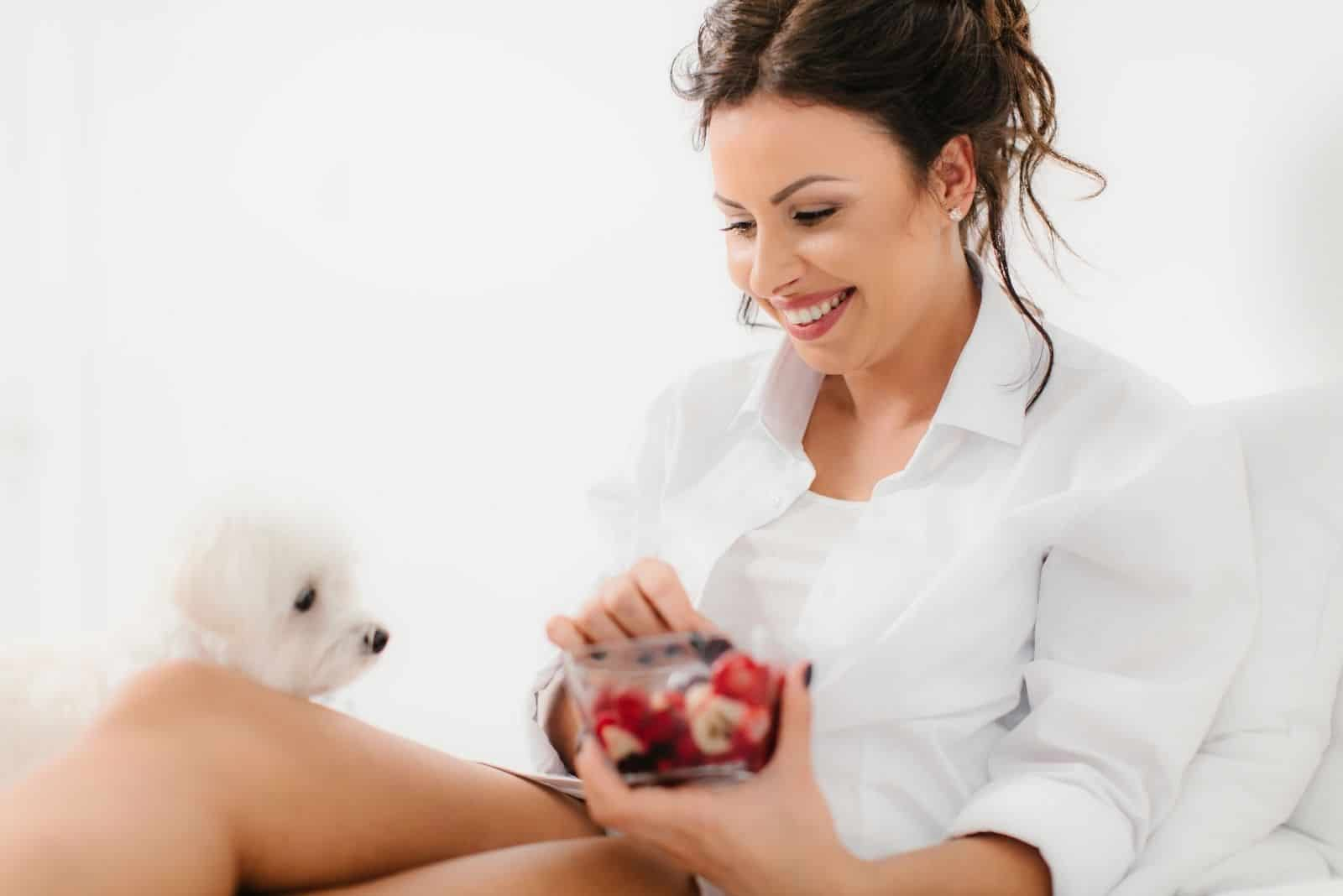 beautiful young woman eating fruits with her dog