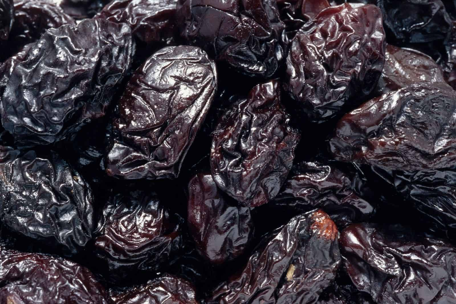 dried black prunes in close up photography