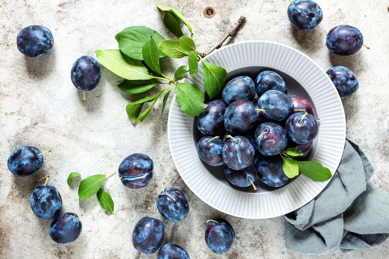 fresh plums on bowl with leaves on the table