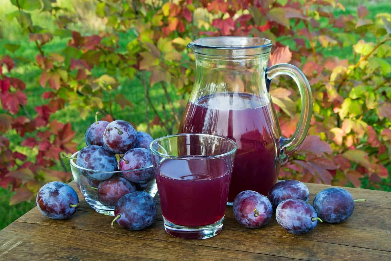 prune juice in the carafe with fresh plums on the glass