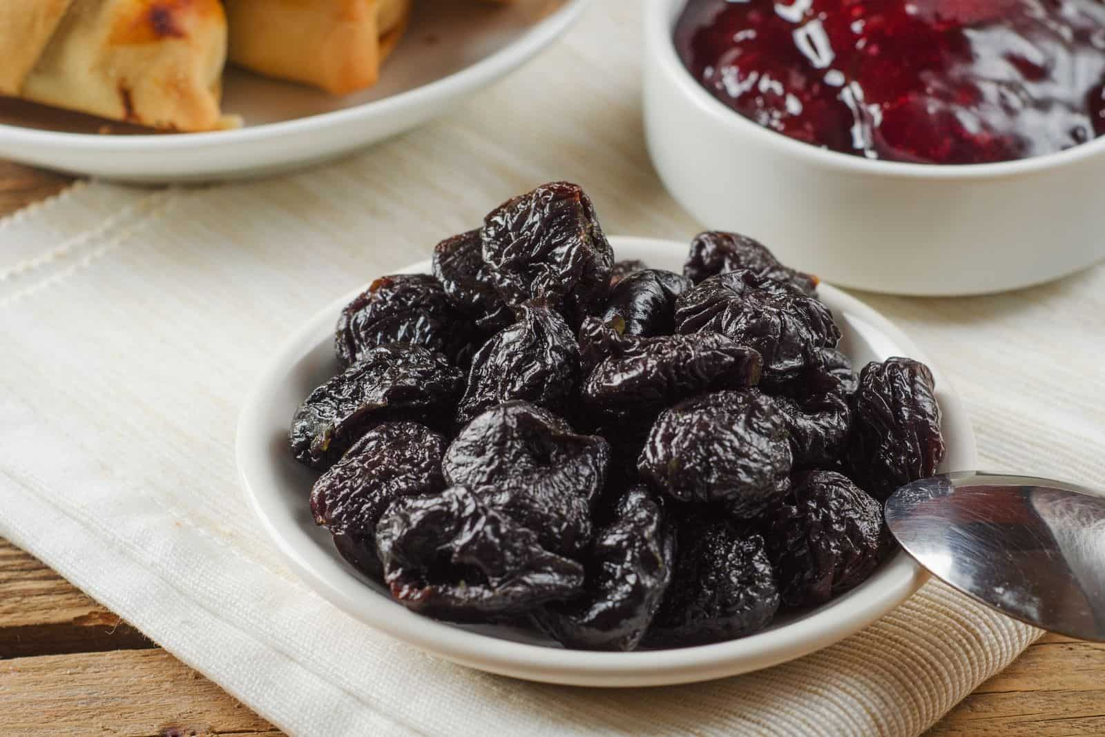 prunes in small plate and jam beside on the table