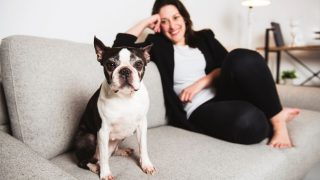 A Woman with is Boston Terrier on the living room