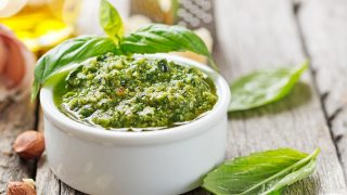 pesto sauce in a white bowl on top of the table