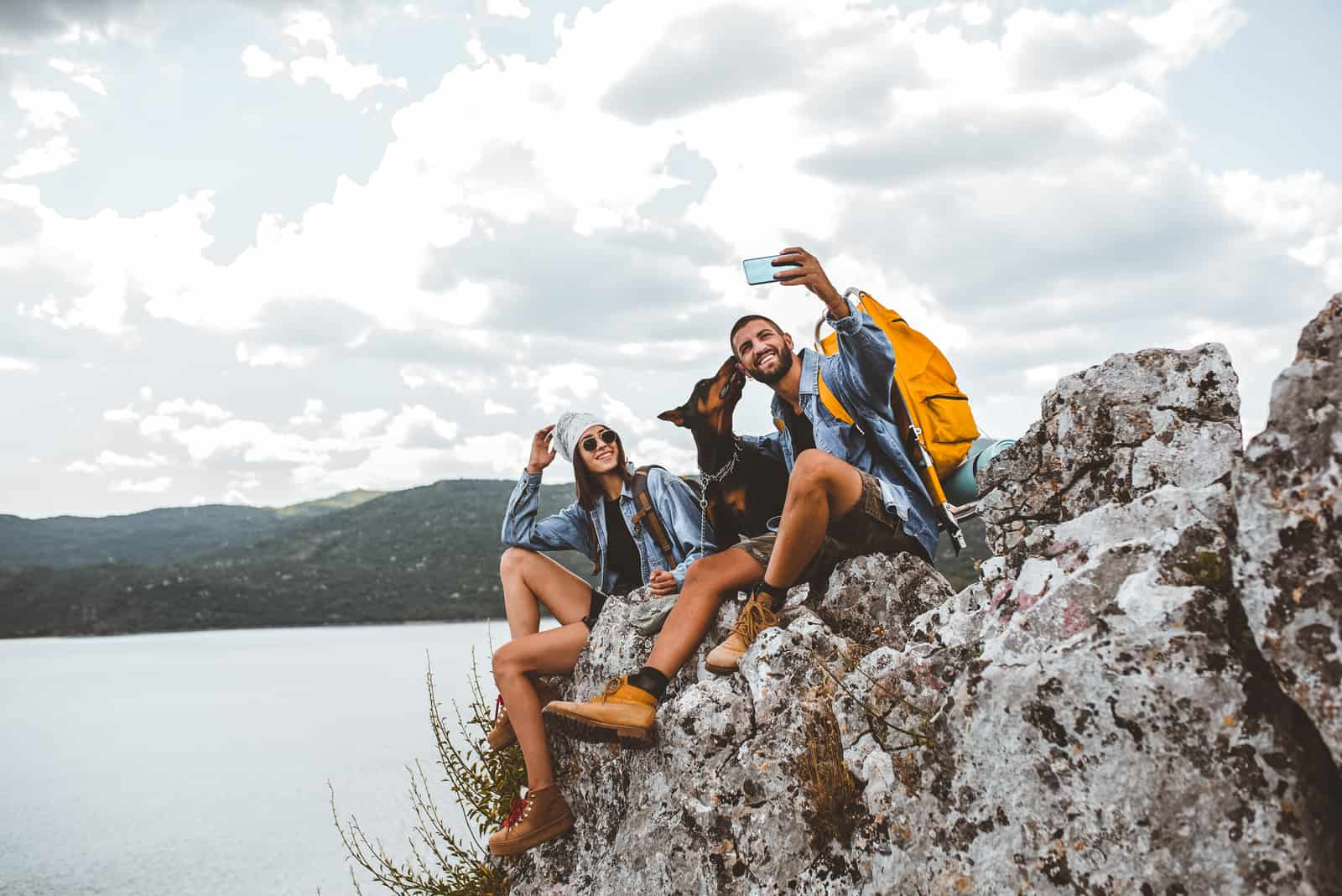 Hikers with backpacks and their doberman sitting