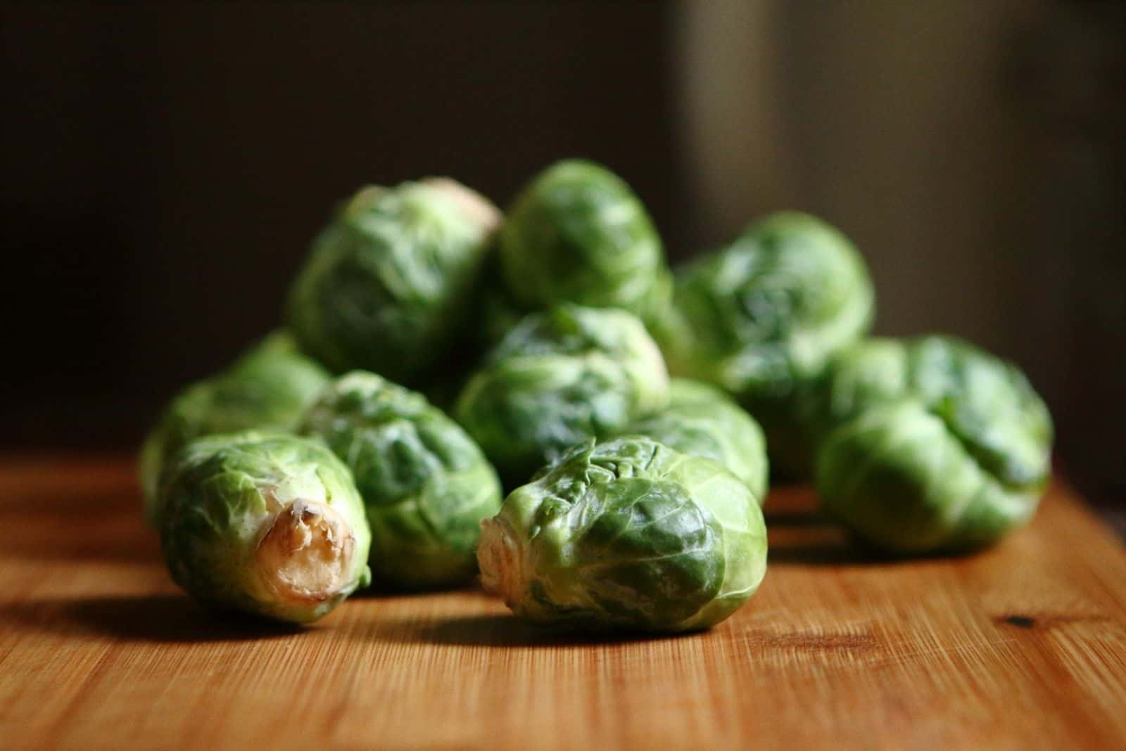 few brussel sprouts on top of the wooden table
