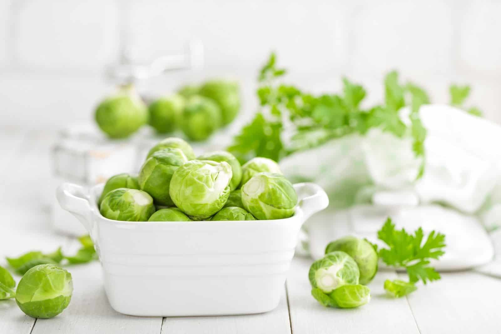 fresh brussel sprouts in a white square bowl