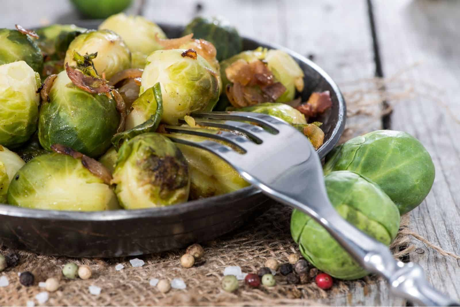 fried brussel sprouts with ham and onion on the plate with a fork