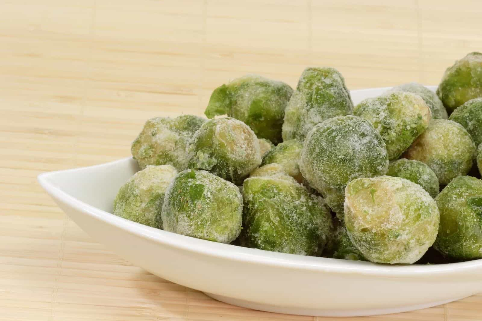 frozen brussel sprouts on a white platewith bright background