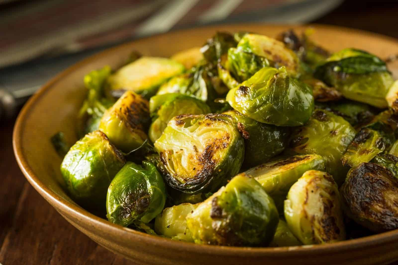 homemade roasted green brussel sprouts placed in a wooden plate