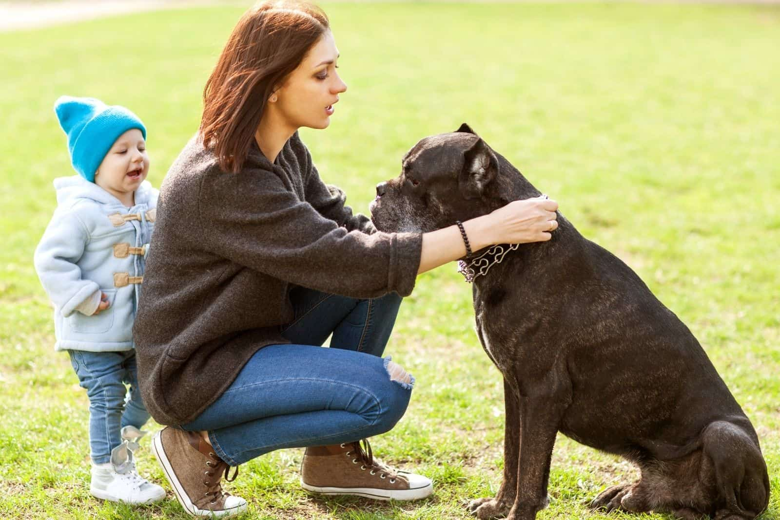 mother and daughter petting a cane corso in the park