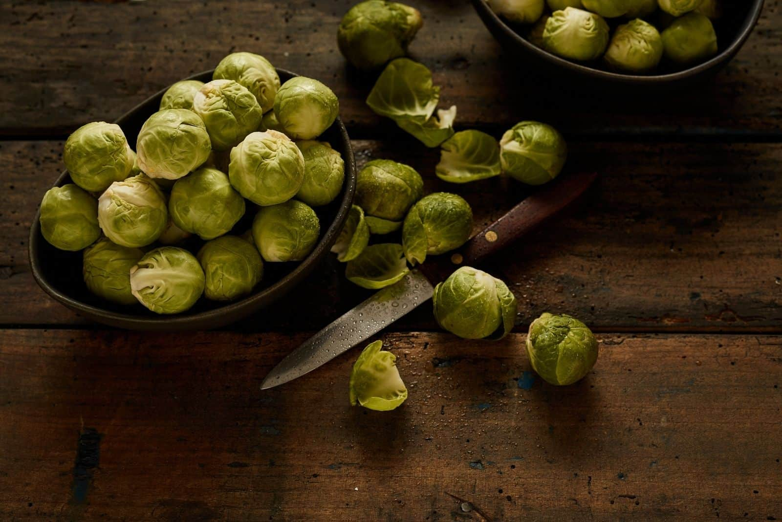 raw brussel sprouts with a knife on top of the table