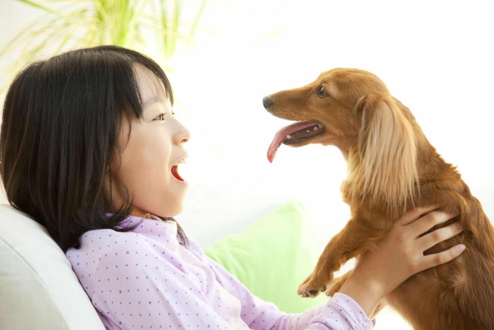 smiling girl hugging a miniature dachshund