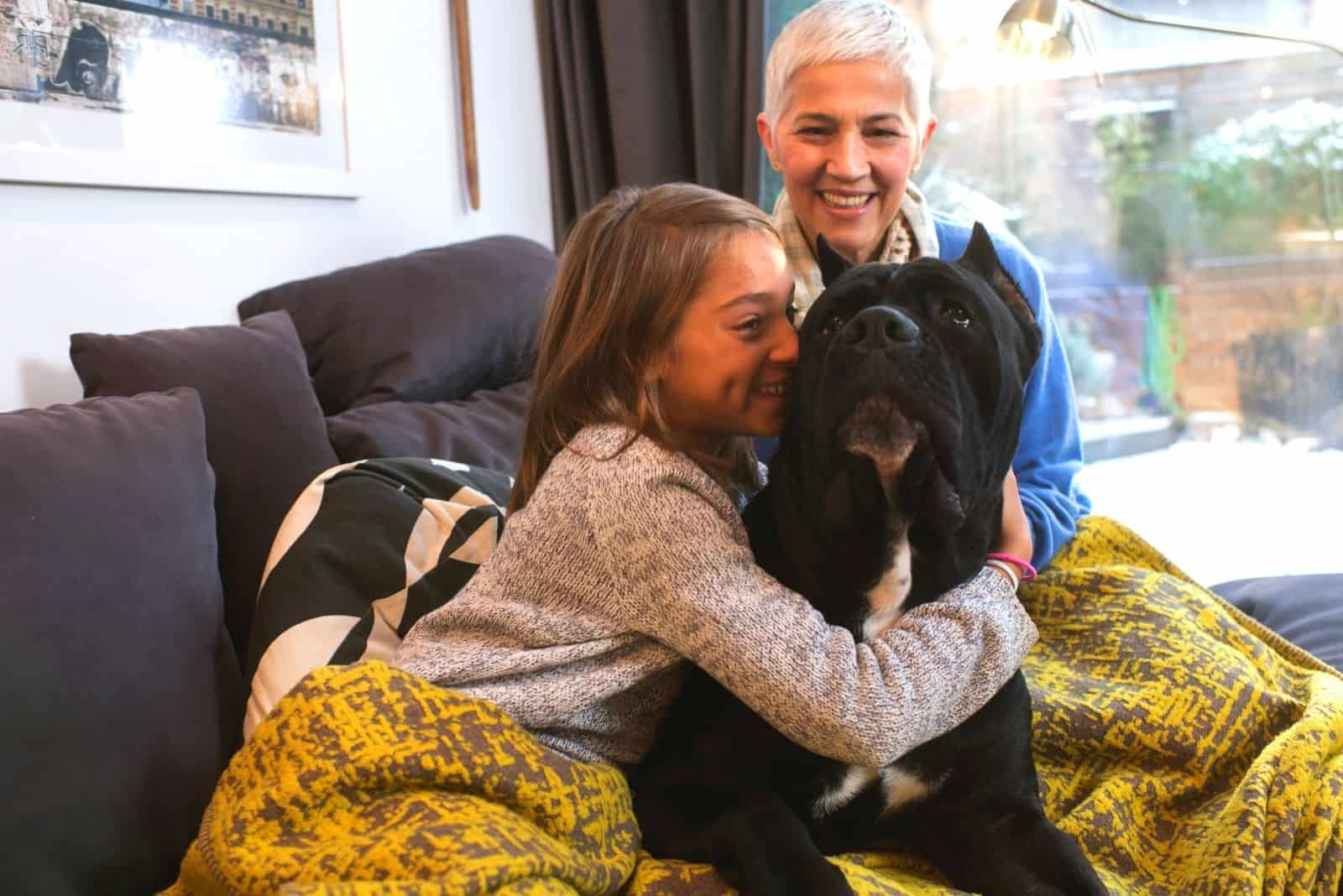 cane corso cuddled by a young kid with her grandmother in the livingroom's sofa