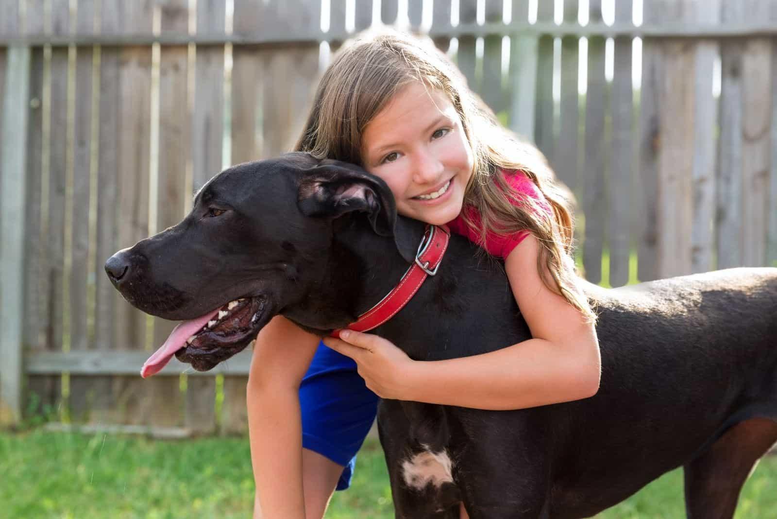 kid hugging dog black great dane mix