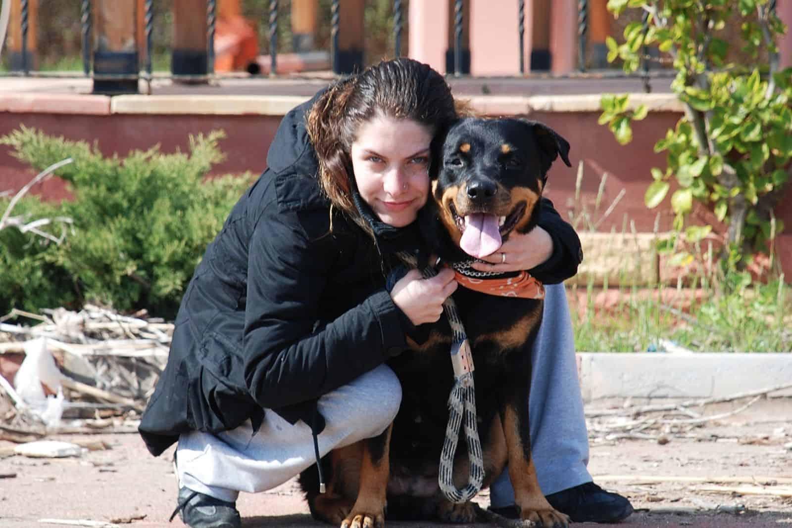 pretty woman hugging a sweet rottweiler dog outdoors