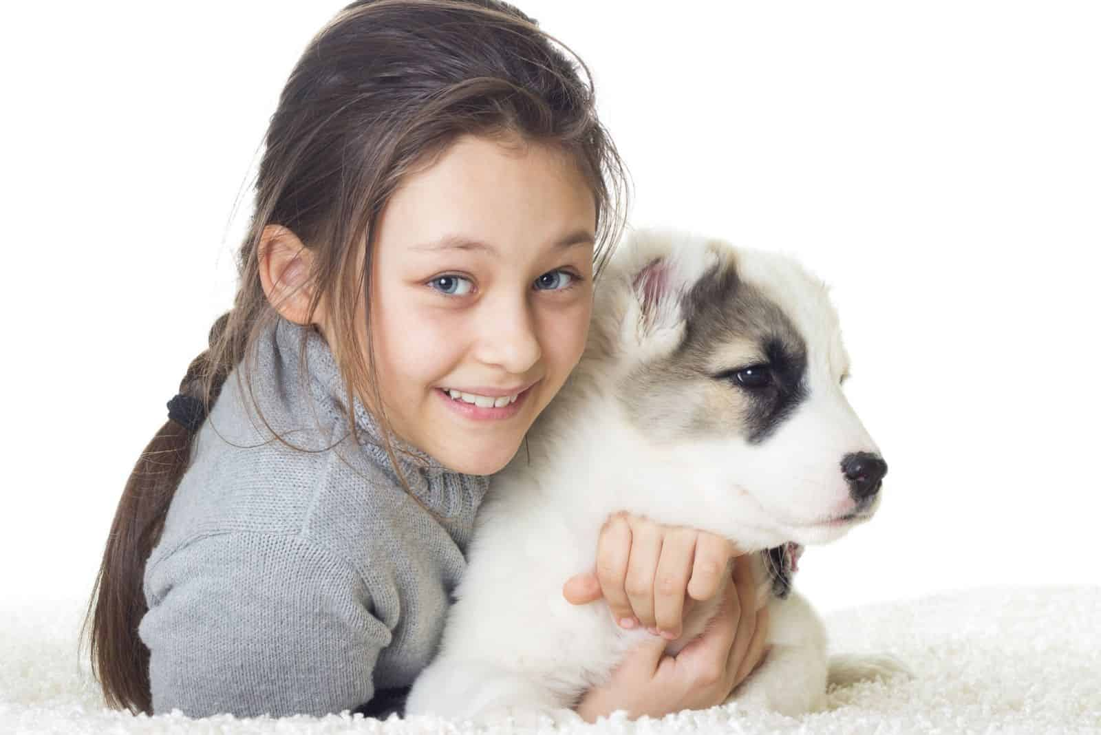 girl embracing a puppy a white german shephed with black markings