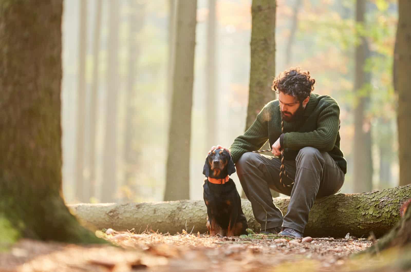 man petting his hunting dog