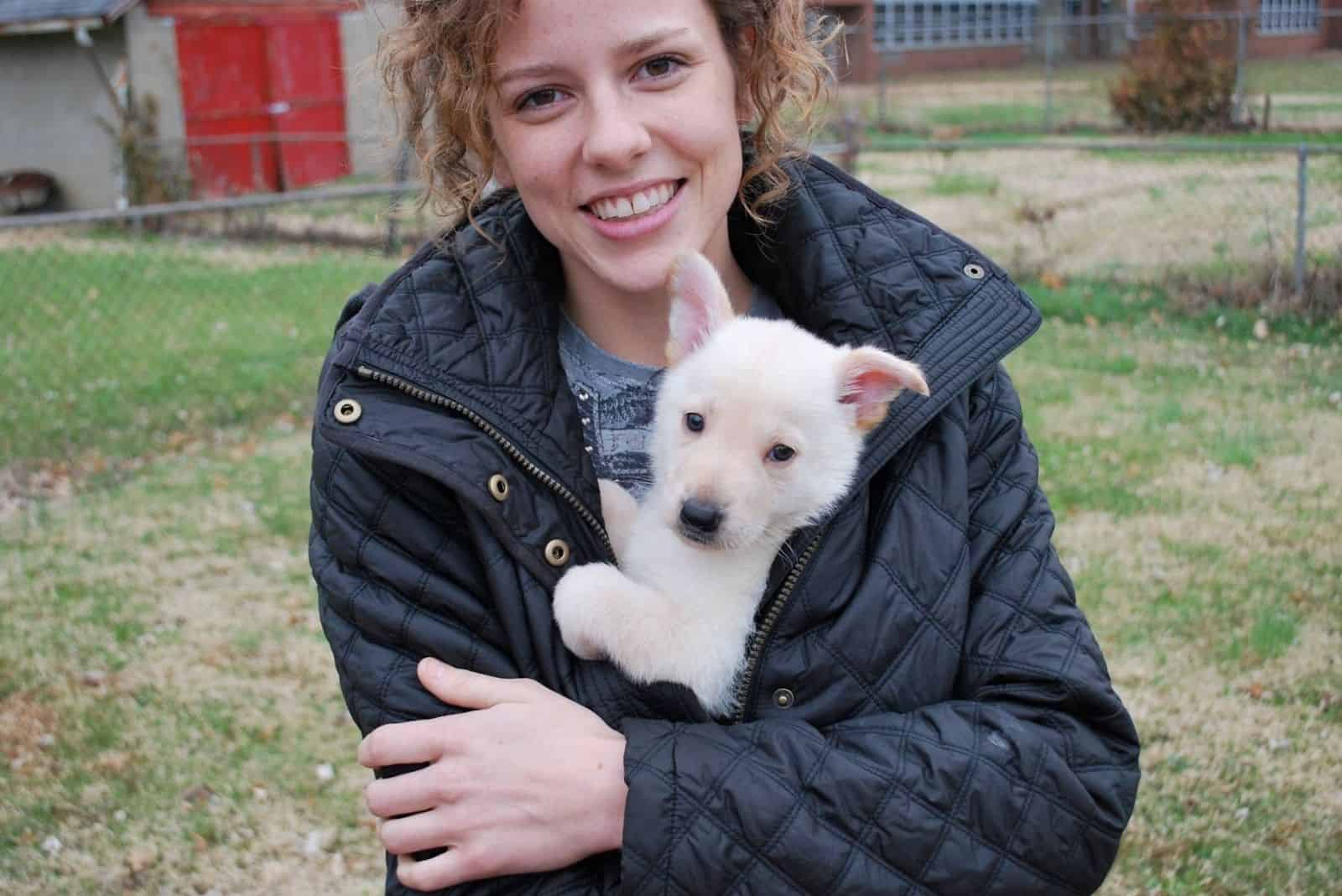 woman holding pet in her arms a white german shepherd puppy