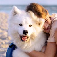 girl hugging her samoyed pet