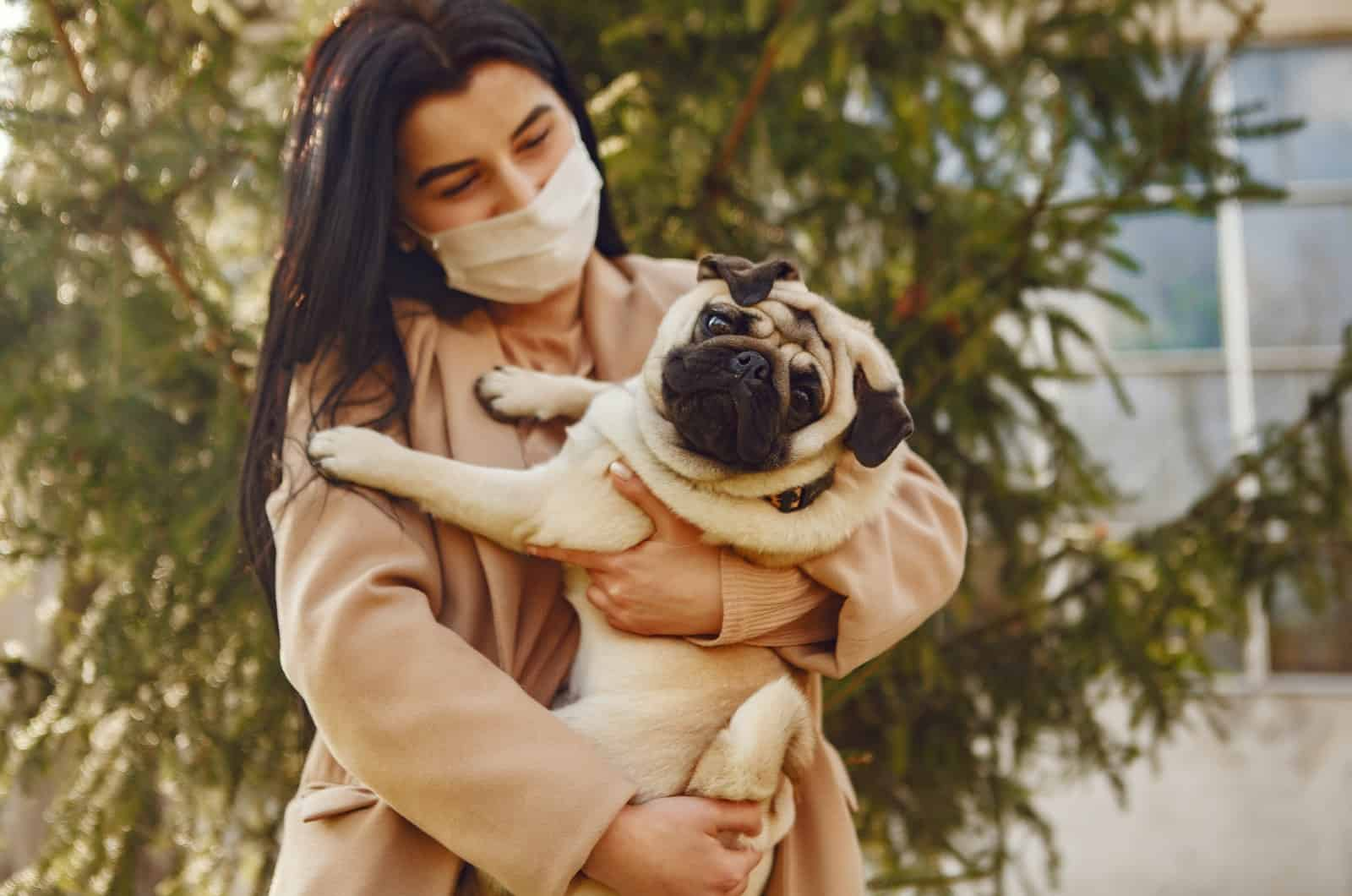 woman holding her pet pug